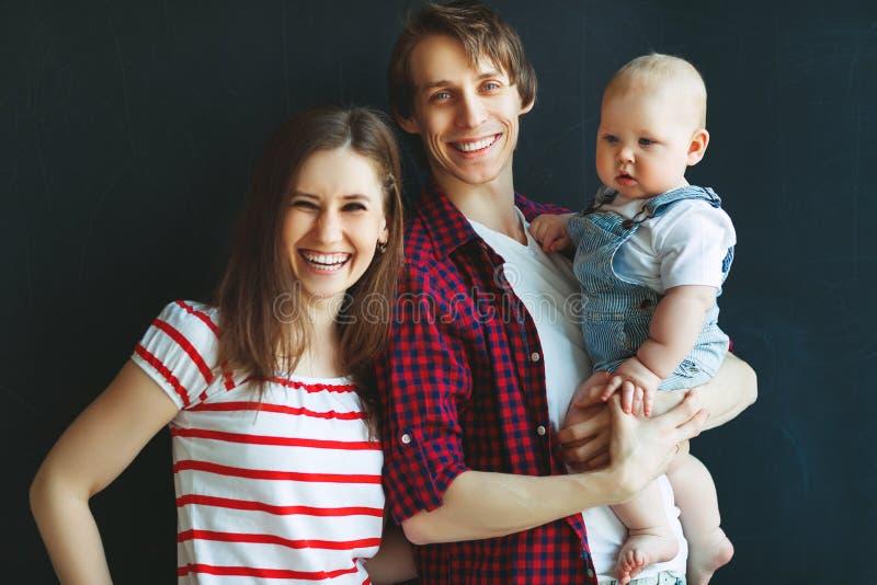 Счастливые мать отца семьи и сын младенца на черной предпосылке стоковые изображения rf