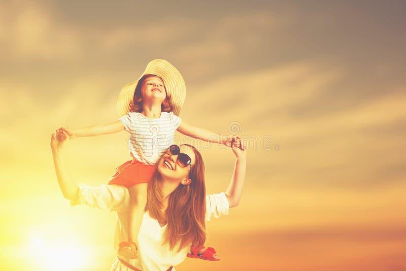 Счастливые мать семьи и дочь ребенка на пляже на заходе солнца стоковое изображение rf