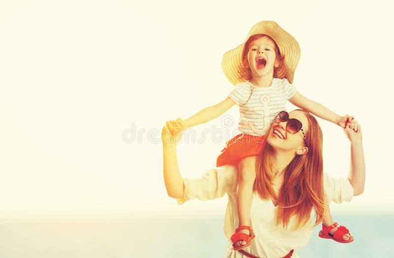 Счастливые мать семьи и дочь ребенка на пляже на заходе солнца