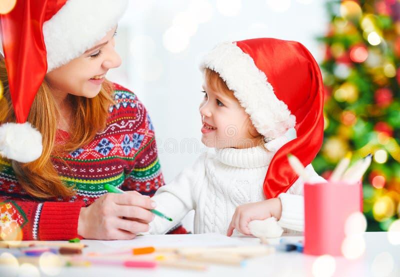 Счастливые мать семьи и дочь ребенка пишут aletter к Санте o стоковые изображения rf