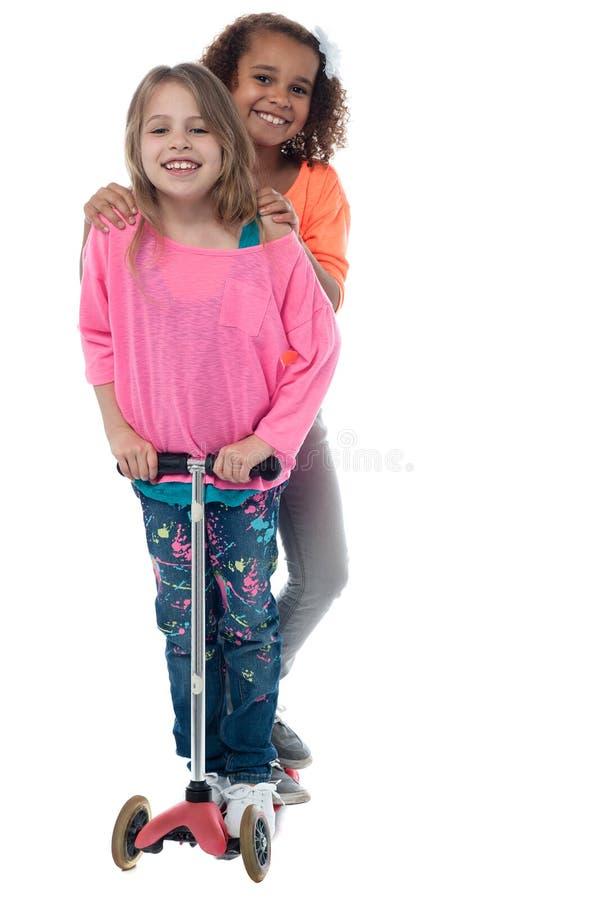 Счастливые маленькие девочки на самокате стоковые изображения rf