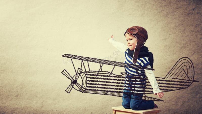 Счастливые мечты младенца быть пилотным авиатором и играми с pla стоковая фотография