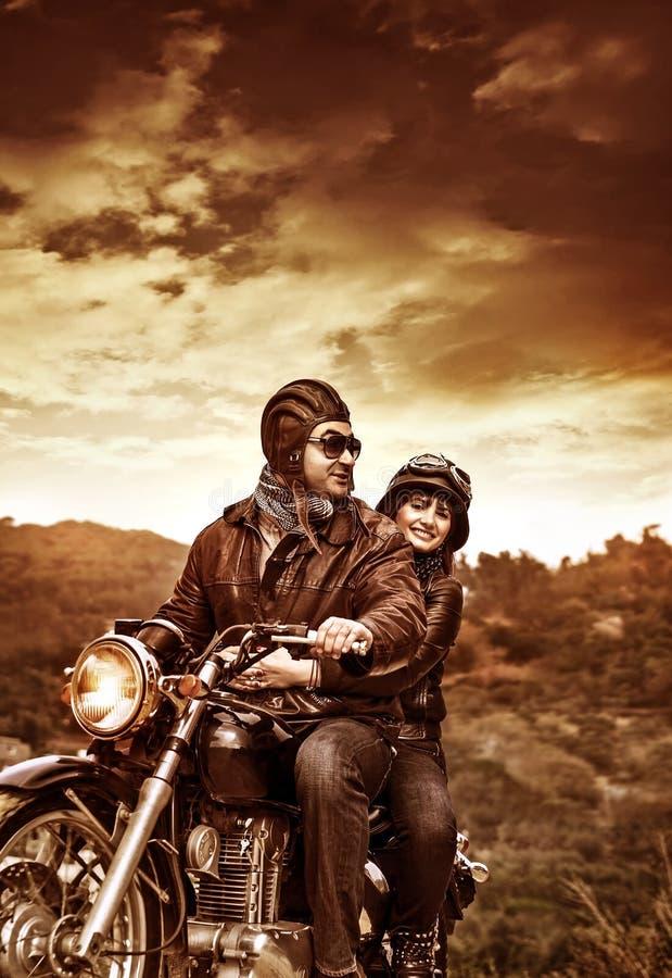 Счастливые мотоциклисты в заходе солнца стоковые изображения