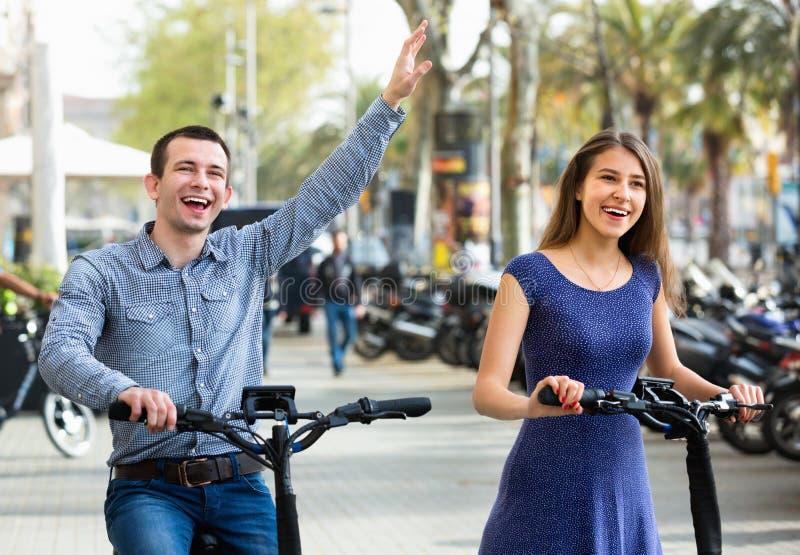 Счастливые молодой человек и женщина с велосипедами electrkc стоковое изображение