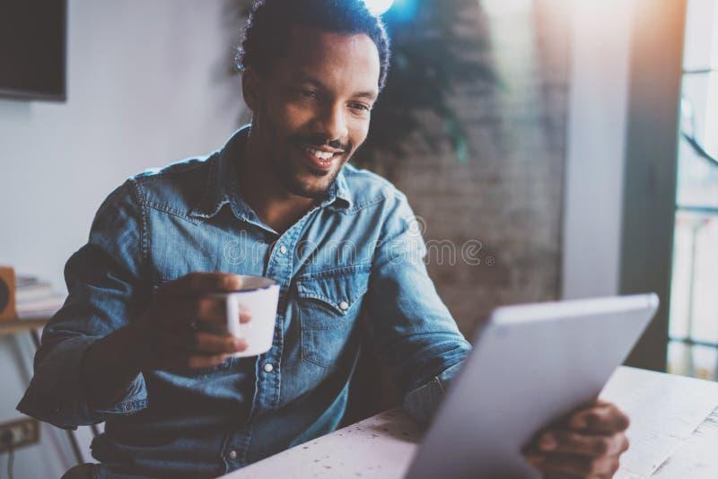 Счастливые молодые африканские мировые новости чтения человека цифровой таблеткой пока сидящ на таблице на солнечном утре Концепц стоковое изображение