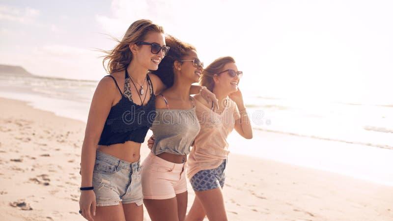 Счастливые молодые женщины гуляя вдоль береговой линии стоковое фото rf