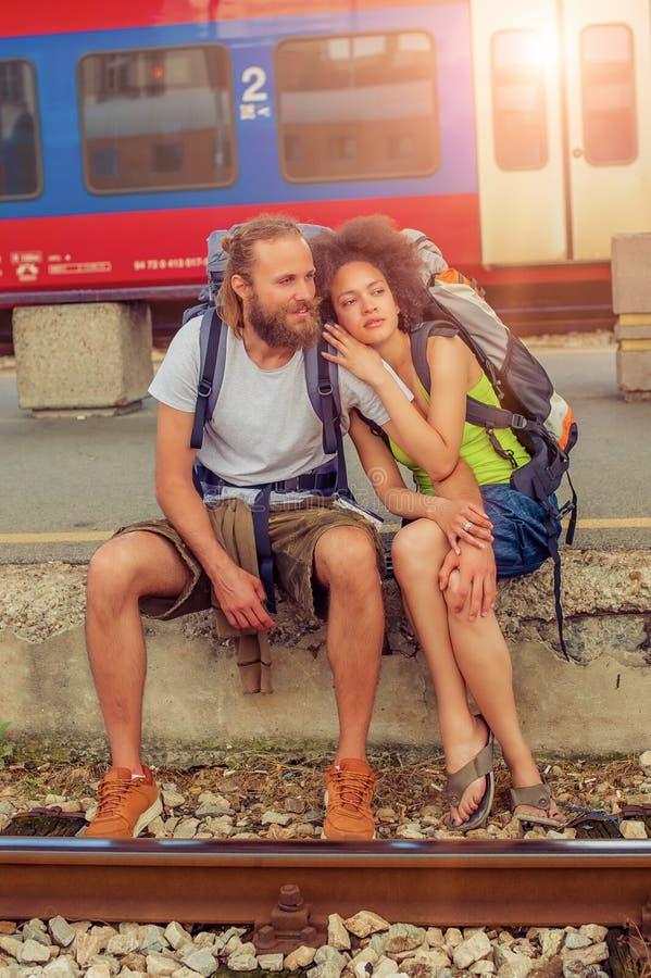 Счастливые молодые и красивые пары туристов сидя на рельсе стоковые фотографии rf