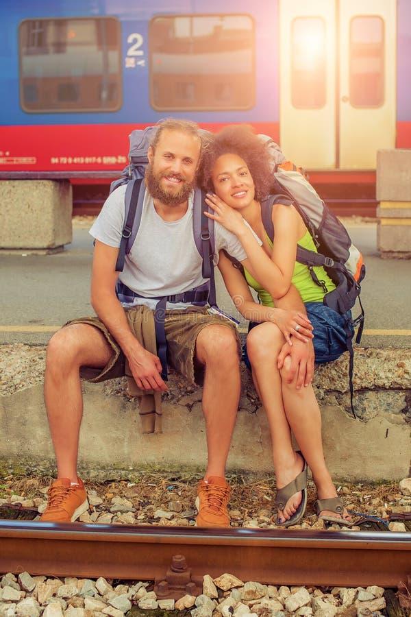 Счастливые молодые и красивые пары туристов сидя на рельсе стоковая фотография rf