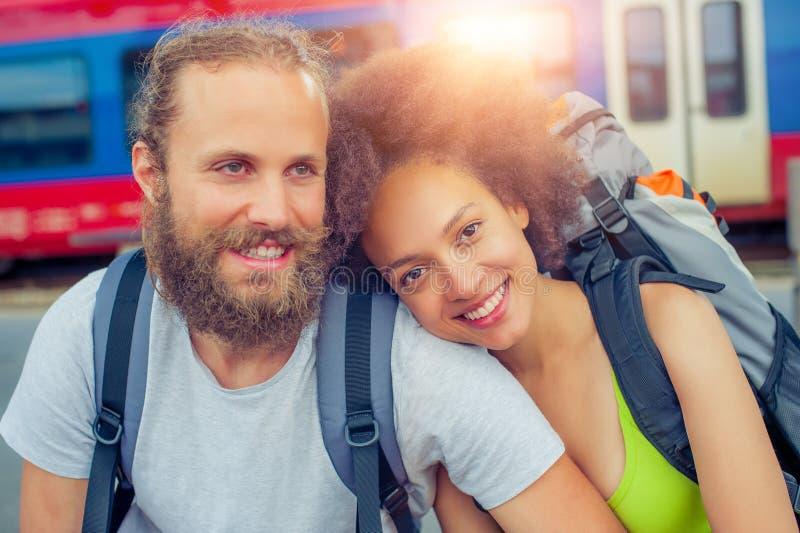 Счастливые молодые и красивые пары туристов сидя на рельсе стоковое фото rf