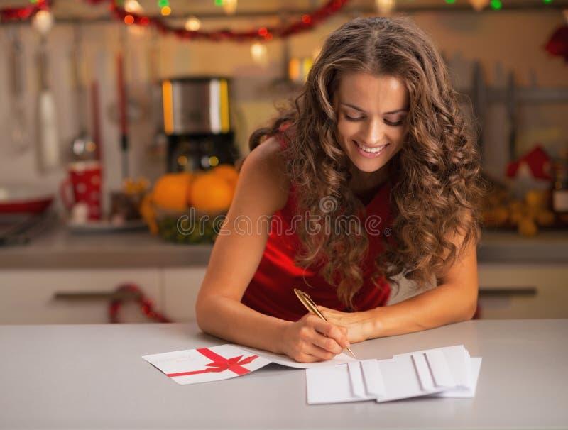 Счастливые молодые открытки рождества подписания домохозяйки в кухне стоковая фотография