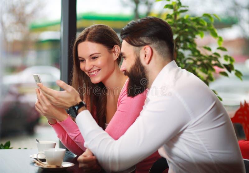 Счастливые молодые пары в кафе смотря в умный телефон стоковое фото rf