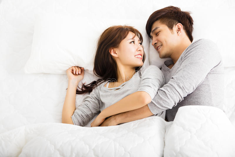 Счастливые молодые пары лежа в кровати стоковое изображение rf