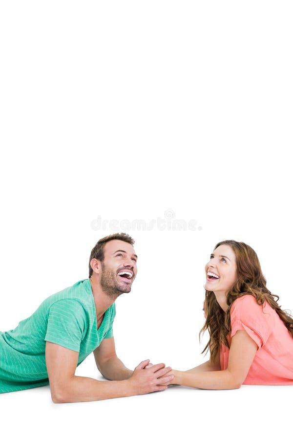 Счастливые молодые пары лежа на поле смотря вверх стоковое фото rf