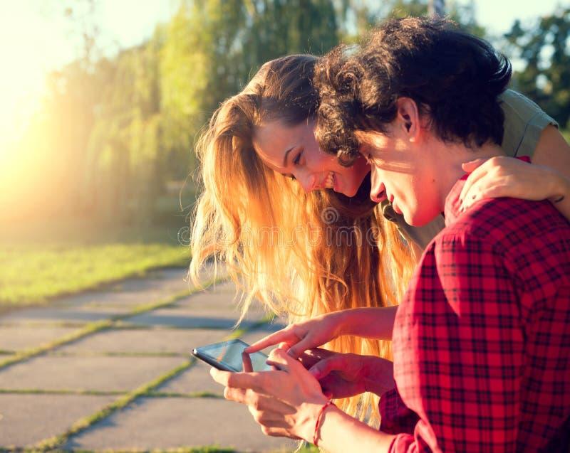 Счастливые молодые пары играя на таблетке совместно стоковая фотография