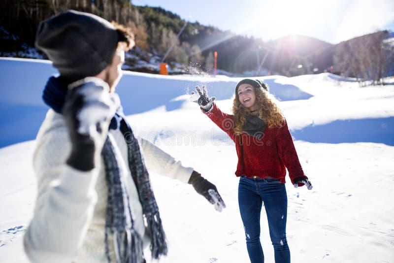 Счастливые молодые пары имея потеху над предпосылкой зимы стоковые изображения rf