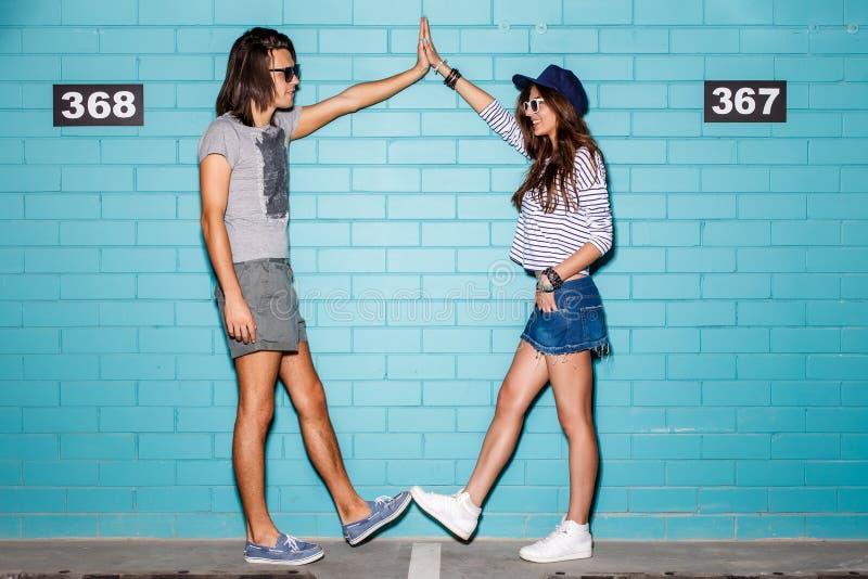 Счастливые молодые пары имея потеху перед голубой кирпичной стеной стоковая фотография rf