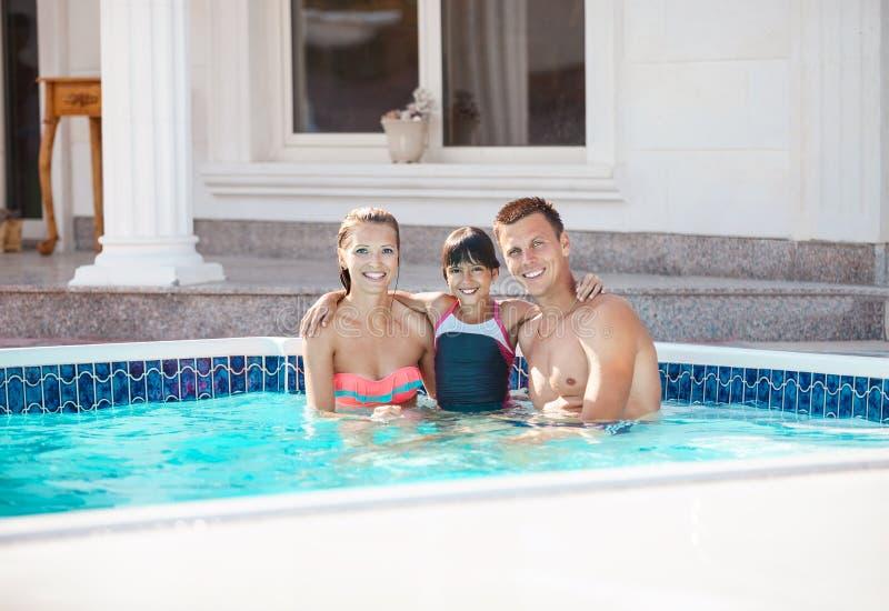 Счастливые молодые пары и дочь в бассейне около роскошной виллы стоковые фотографии rf