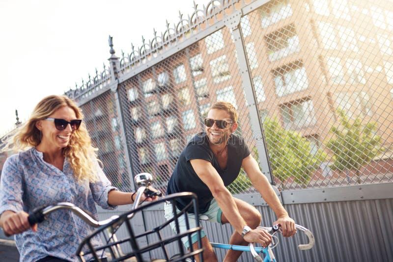 Счастливые молодые пары наслаждаются ездой велосипеда лета стоковые фото