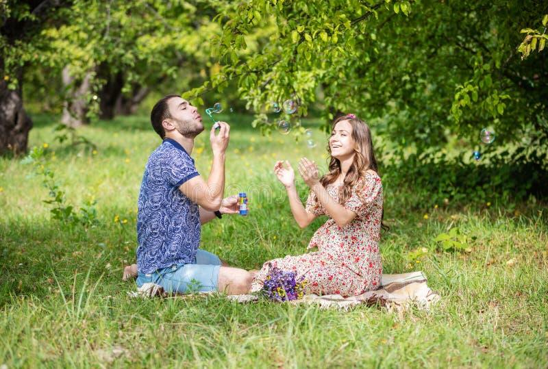 Счастливые молодые пары надеясь младенца, беременной женщины с пузырями супруга дуя и смеяться над стоковые изображения