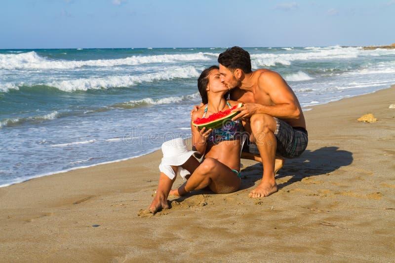 Счастливые молодые пары на песчаном пляже на сумраке стоковые изображения