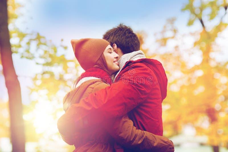 Счастливые молодые пары обнимая в парке осени стоковые фотографии rf