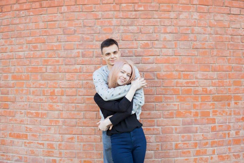 Счастливые молодые пары обнимая и усмехаясь на предпосылке красной кирпичной стены Белокурая девушка с голубыми глазами и молодой стоковые изображения