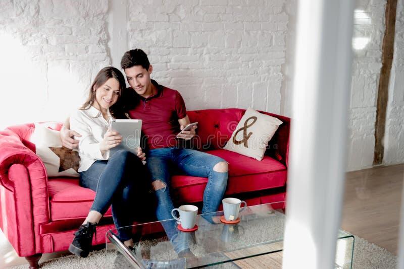 Счастливые молодые пары ослабили дома с таблеткой стоковое фото