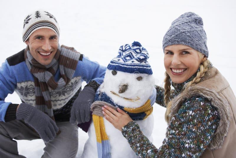 Счастливые молодые пары одевая снеговик стоковое фото