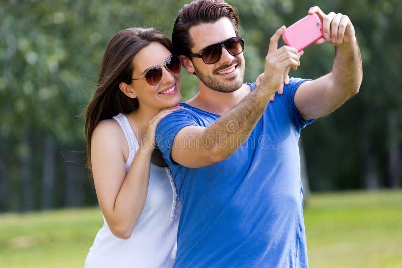 Счастливые молодые пары принимая selfies с ее smartphone в равенстве стоковое изображение rf