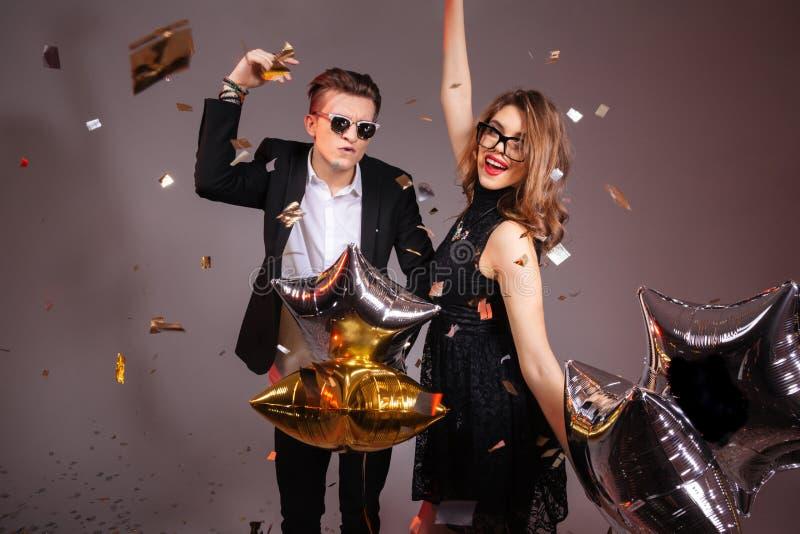 Счастливые молодые пары при воздушные шары танцуя и имея партия стоковые фотографии rf