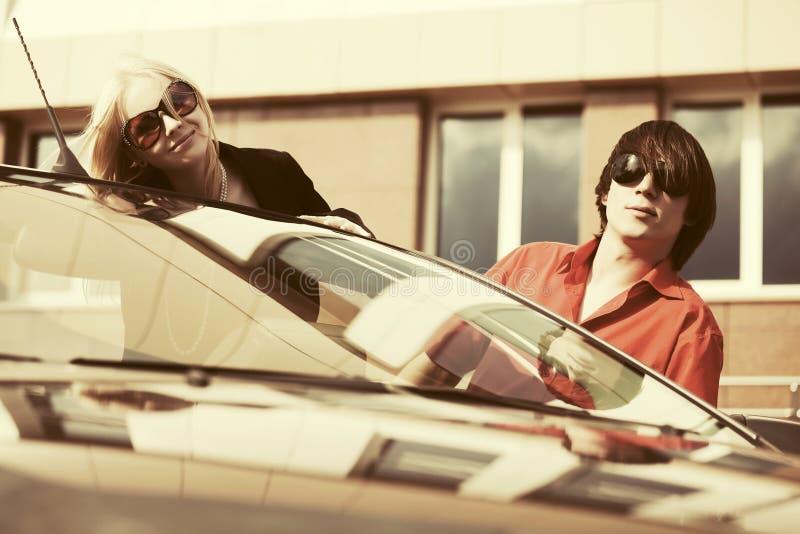 Счастливые молодые пары рядом с обратимым автомобилем стоковое изображение