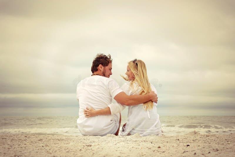 Счастливые молодые пары сидя океаном на пляже стоковое изображение rf