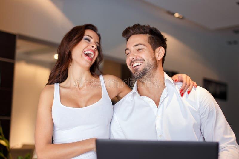 Счастливые молодые пары смеясь над дома стоковое изображение