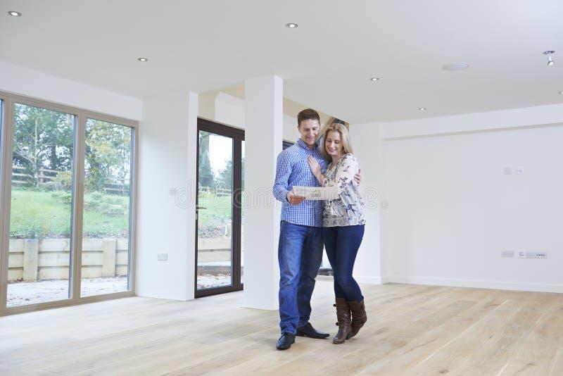 Счастливые молодые пары смотря детали нового дома стоковые изображения