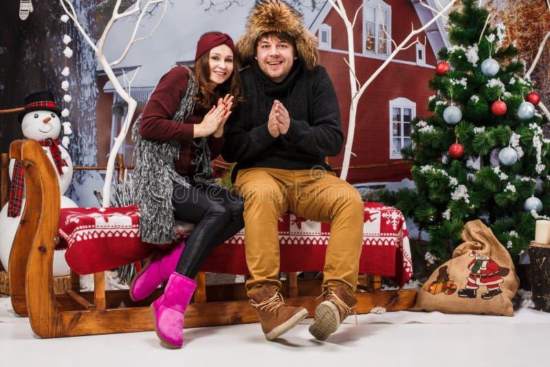 Счастливые молодые пары с деревом ecorations Christmasd дома стоковое фото