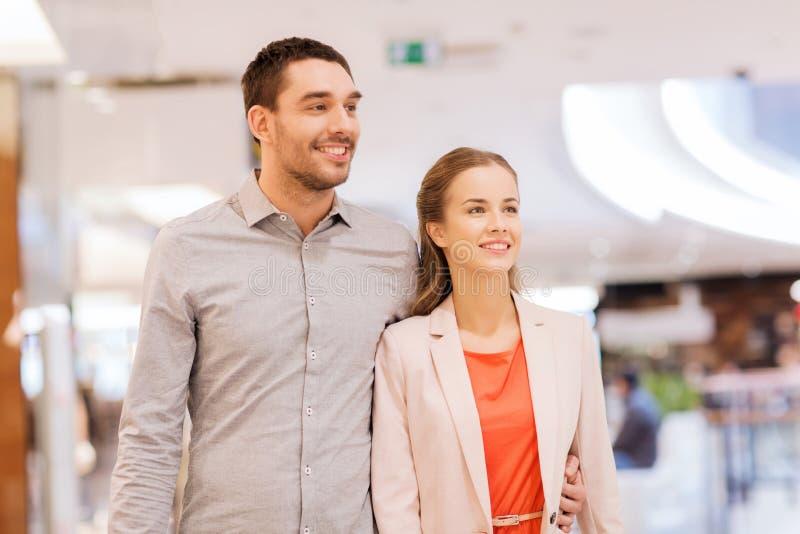 Счастливые молодые пары с хозяйственными сумками в моле стоковое фото