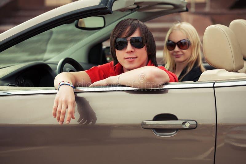 Счастливые молодые пары управляя обратимым автомобилем стоковое изображение rf