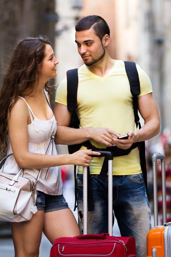 Счастливые молодые путешественники находя путь с телефоном стоковые изображения rf