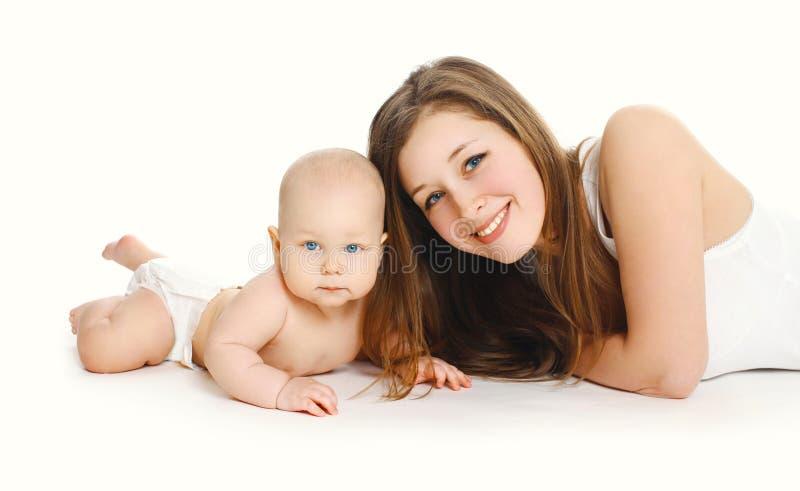 Счастливые молодые усмехаясь мать и младенец совместно на белизне стоковые изображения