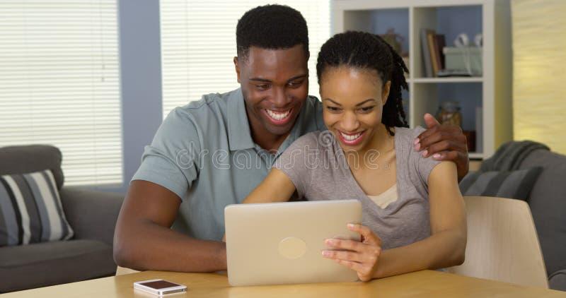 Счастливые молодые черные пары используя таблетку совместно смеясь над стоковое фото rf