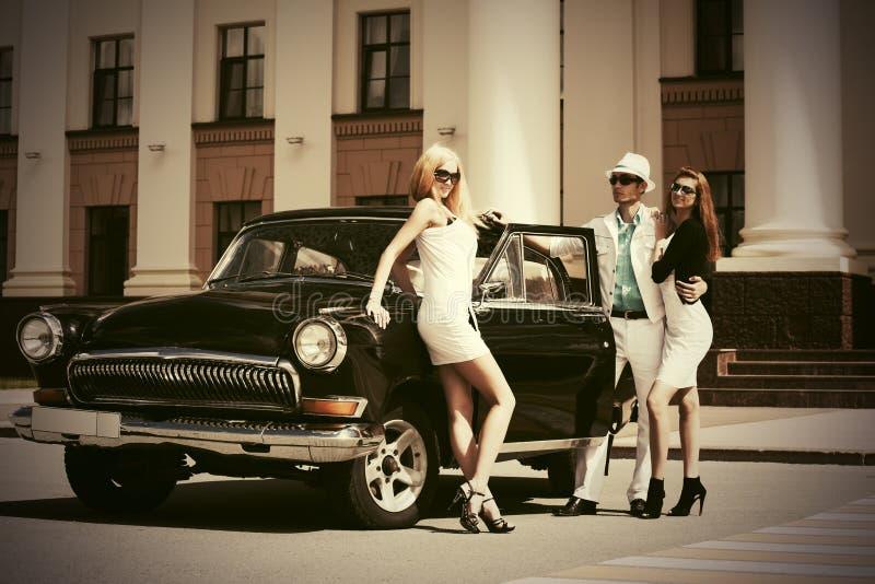 Счастливые молодые люди моды рядом с винтажным автомобилем стоковое изображение