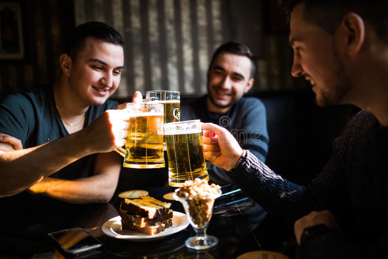 Счастливые мужские друзья выпивая пиво и clinking стекла на баре или пабе стоковые фотографии rf