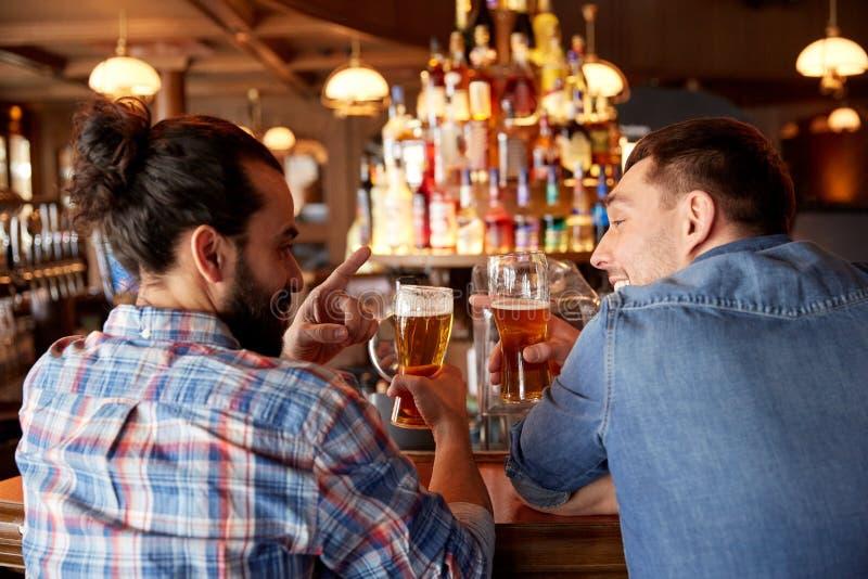 Счастливые мужские друзья выпивая пиво на баре или пабе стоковое фото