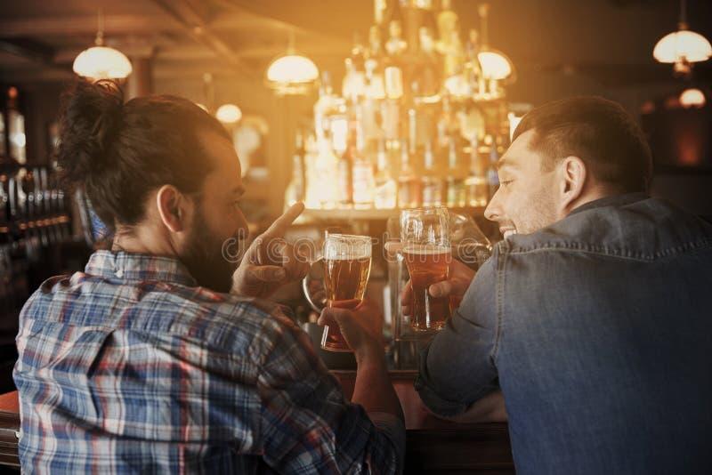 Счастливые мужские друзья выпивая пиво на баре или пабе стоковые фотографии rf