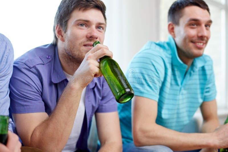 Счастливые мужские друзья выпивая пиво дома стоковое фото