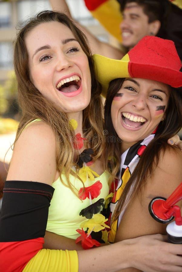 Счастливые немецкие поклонники футбола девушки празднуя стоковые изображения