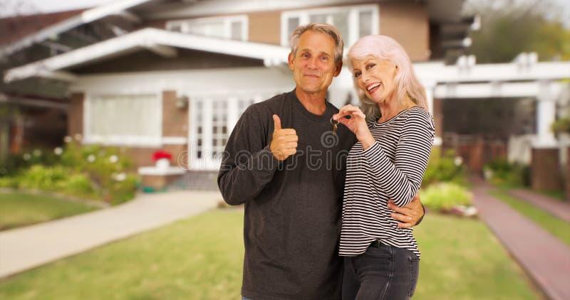 Счастливые новые старшие домовладельцы усмехаясь на камере стоковое фото
