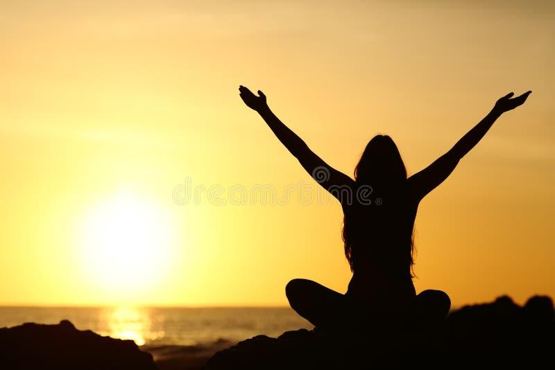 Счастливые оружия повышения женщины смотря восход солнца стоковые фото