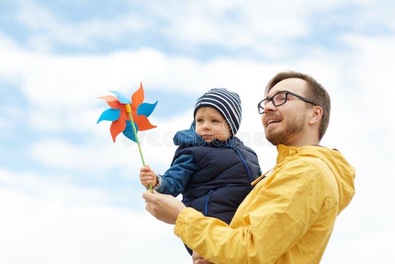Счастливые отец и сын с pinwheel забавляются outdoors стоковое фото rf