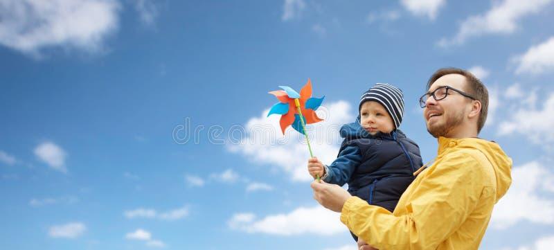 Счастливые отец и сын с pinwheel забавляются outdoors стоковые фотографии rf